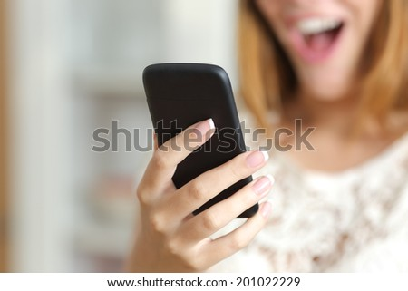 Close up of a surprised woman hand holding and using a smart phone at home             - stock photo