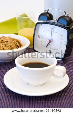 Close-up of a table and wonderful cup of hot coffee, alarm clock