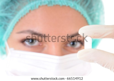 Close-up of a tablet in doctor's hands in gloves with female face out of focus on background - stock photo