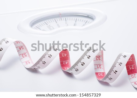 Close-up of a tape measure and Bathroom scale - stock photo