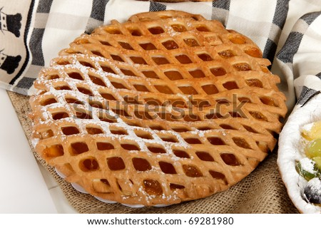 Close up of a tasty sweet fruits pie on a kitchen towel. Studio shot. White background.