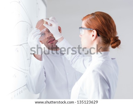 close-up of a teacher and his student in a lab analyzing a transparent pill in front of a whiteboard