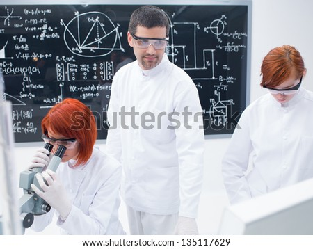 close-up of a teacher supervising two students during their lab experiments in a chemistry lab with a blackboard on the background - stock photo