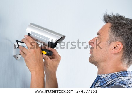 Close-up Of A Technician Adjusting Cctv Camera On Wall - stock photo