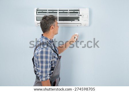 Close-up Of A Technician Operating Air Conditioner With Remote Controller
