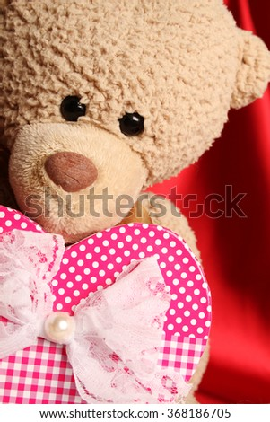Close up of a teddy bear holding a big gift box as heart - stock photo