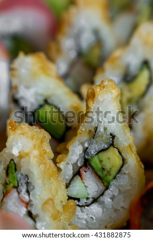 close up of a tempura fried sushi roll with fresh crab and avocado - stock photo