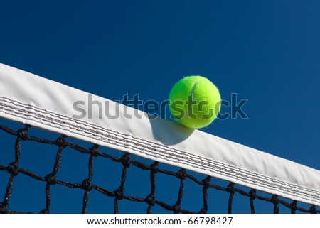 Close-up of a tennis ball touching the net tape with a blue sky background. - stock photo