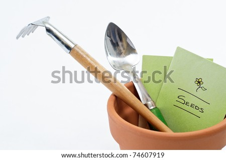 Close up of a terracotta plant pot containing seed packet and potting tools. - stock photo