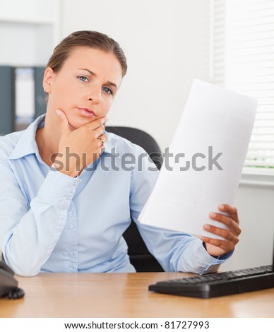 Close up of a thinking businesswoman holding a paper in her office