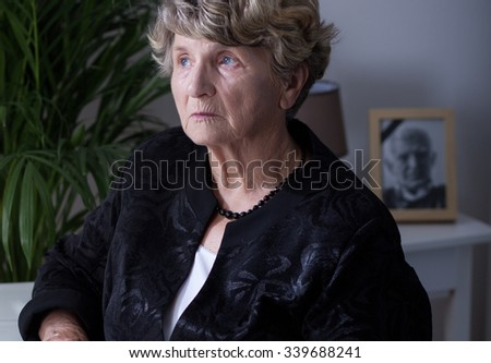 Close-up of a thoughtful elderly widow at home - stock photo
