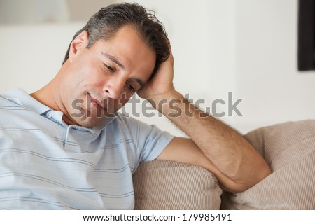 Close-up of a thoughtful man sitting on sofa in the living room at home