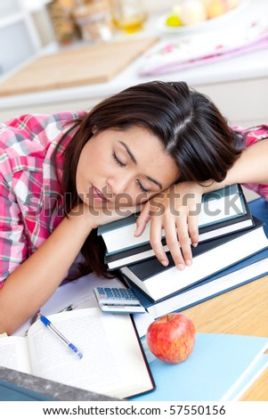 Close-up of a tired caucasian teen girl studying at home - stock photo