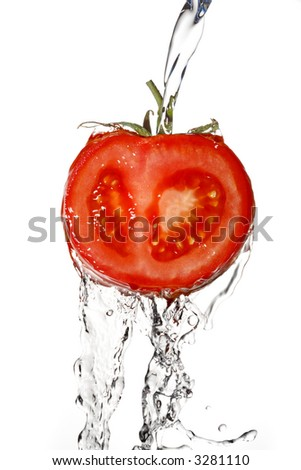 close up of a tomato with pouring water - stock photo