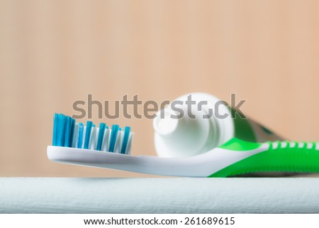 Close-up of a toothbrush and tube of toothpaste on the edge of a bathroom counter from a low angle view. - stock photo