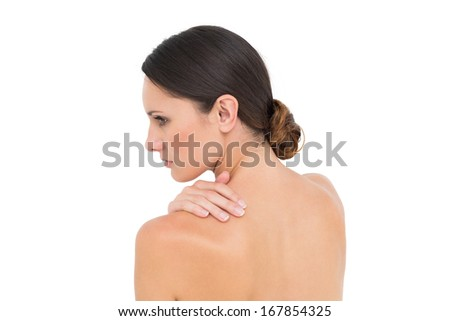 Close-up of a topless young woman with shoulder pain over white background - stock photo