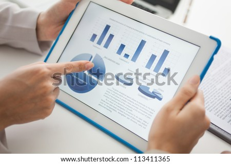 Close-up of a touchscreen with financial data in form of charts and diagrams - stock photo