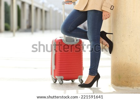 Close up of a tourist woman legs waiting with a suit case in an airport or station - stock photo