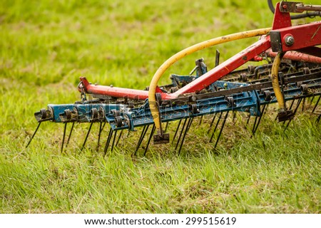 Close up of a tractor working on grass with an air powered harrow. - stock photo