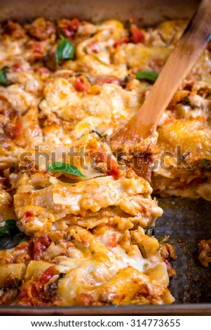 Close-up of a traditional italian lasagna made with minced beef bolognese sauce topped with basil leafs served on a rustic dark wooden table. Selective focus