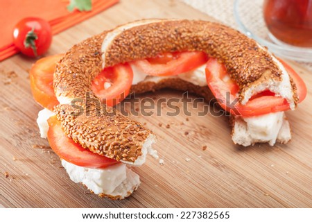 Close up of a traditional Turkish Bagel (simit) sandwich with feta cheese and tomatoes - stock photo