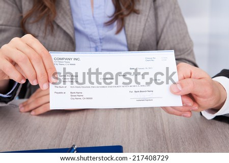 Close-up Of A Two Businesspeople Holding Cheque Over Desk - stock photo