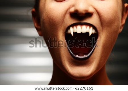 Close up of a vampire woman's mouth over dark background - stock photo