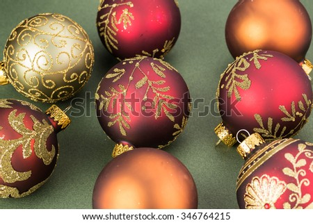 Close up of a variety of Christmas ball ornaments on a green background.