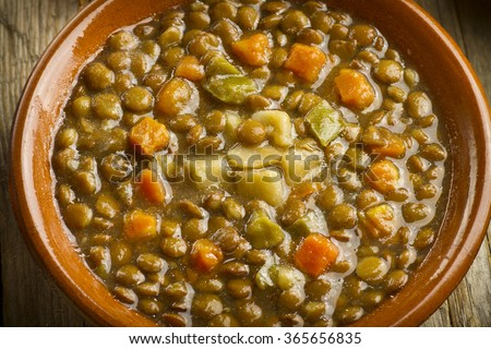 Close up of a vegetable lentil soup on a wooden table, with lentils, carrots, pepper, and potatoes - stock photo