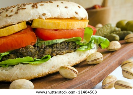 Close up of a vegetarian burger made from lentils and azuki beans, with tomato baked pumpkin slices and lettuce in a whole-grain bread with flax seeds. Focus is at the front. - stock photo