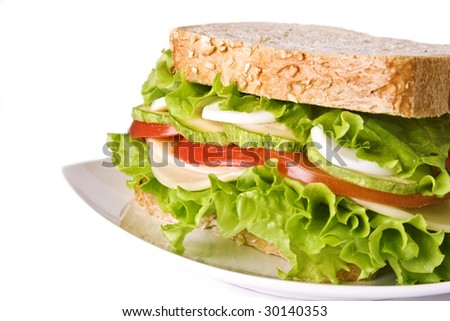 Close up of a vegetarian sandwich containing: lettuce, tomato, cheese, egg, zucchini in a wholegrain slice of bread. Selective focus at the center. - stock photo