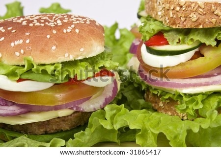 Close up of a veggie burguer containing: soy meat, cheese, lettuce, tomato, cucumber, onion, egg.