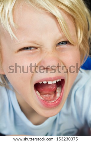 Close-up of a very angry, screaming child having a tantrum - stock photo