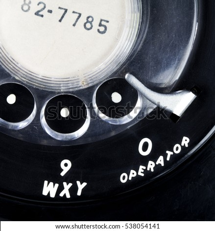 Close up of a vintage black rotary telephone dial with 'operator'.