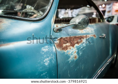 Close up of a vintage blue car with rust