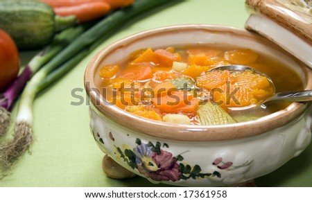 Close up of a vintage ceramic saucepan full of vegetable soup. Focus on the soup. - stock photo