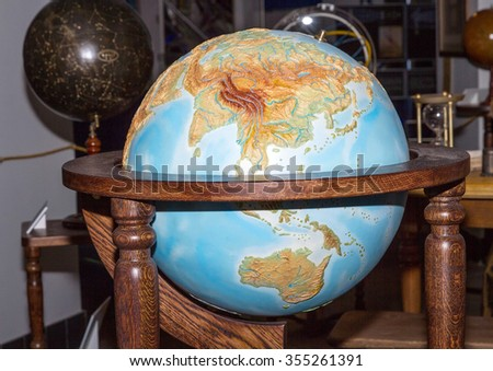 Close-up of a vintage globe on wooden poles . - stock photo