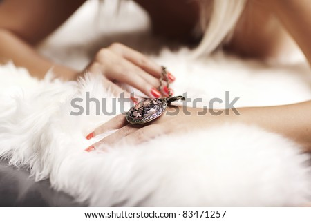 Close-up of a vintage necklace on a girls hand, on a white background.