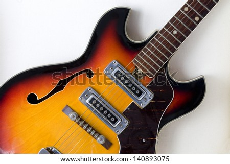 Close up of a vintage traditional semi-hollow electric guitar with f-holes on a white background. Electric Guitar Detail. - stock photo