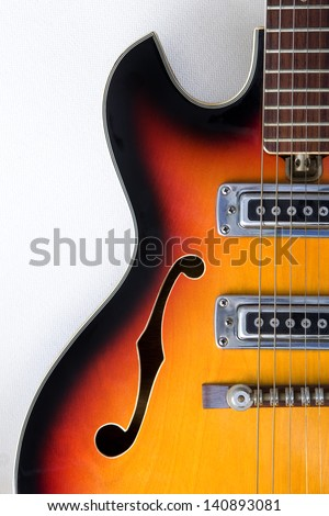 Close up of a vintage traditional semi-hollow electric guitar with f-holes on a white background. Guitar Detail.
