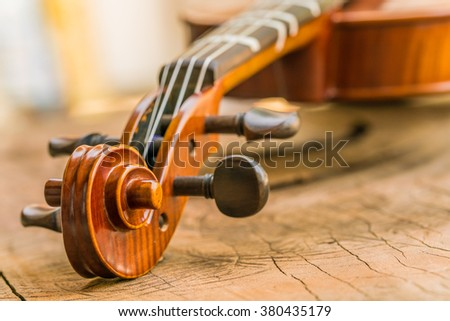 Close up of a violin set up for a beginer on wooden surface