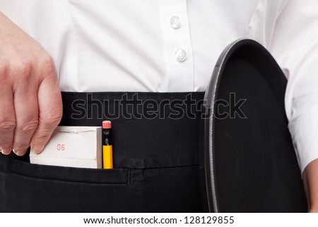 Close up of a waitress taking her order pad out of her apron pocket whilst she holds a tray in the other hand. - stock photo