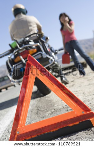 Close-up of a warning triangle with woman and traffic cop - stock photo