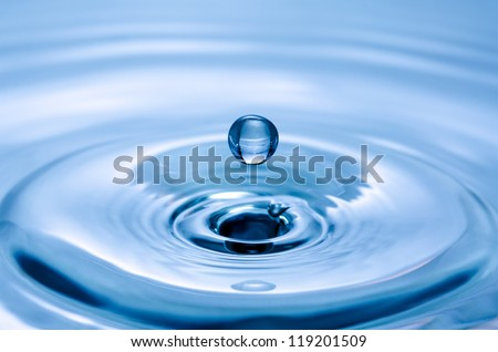 Close-up of a water drop that hits the water surface - stock photo