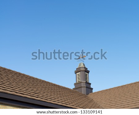 Close up of a weather vane on a roof,wind indicator, over blue sky