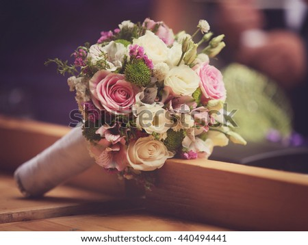 Close up of a wedding bouquet on a wooden table