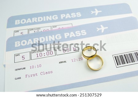 close up of a wedding rings on an airline boarding passes of a honeymoon  - stock photo