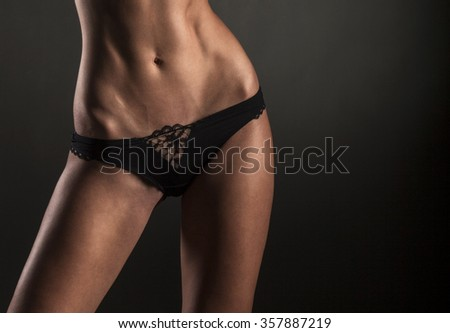 Close-up of a well-groomed and tight stomach of a young woman on a black background