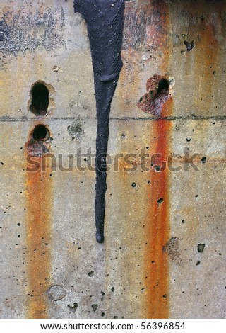 Close up of a wet, weathered concrete sea wall. Pitted surface and two empty bolt holes with rust stains dripping from them. Dried tar has dripped from the top of the frame.