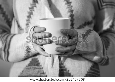 Close up of a white coffee mug being held by a young woman in black and white - stock photo